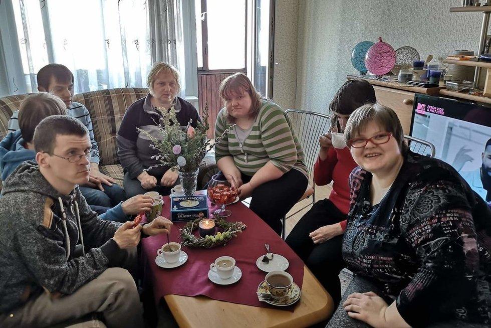 Apsaugoto būsto paslaugų gavėjos Edita (pirmoji iš dešinės) ir Iveta (trečioji iš dešinės) susioraganizavo popietę prie arbatos su draugais iš dienos centro. (K. Kairio nuotr.)
