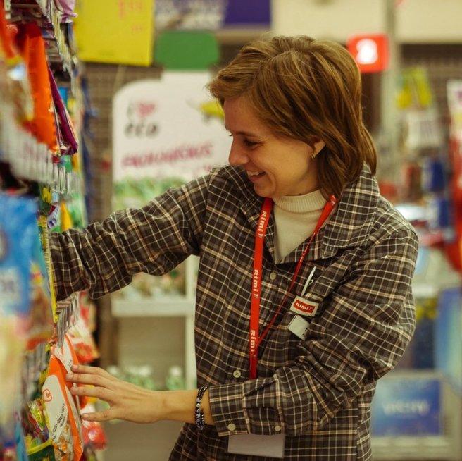 """Tatjana parduotuvėje """"RIMI"""" tikrina kainas, spausdina etiketes, tvarko prekes lentynose. Artūro Morozovo nuotr."""