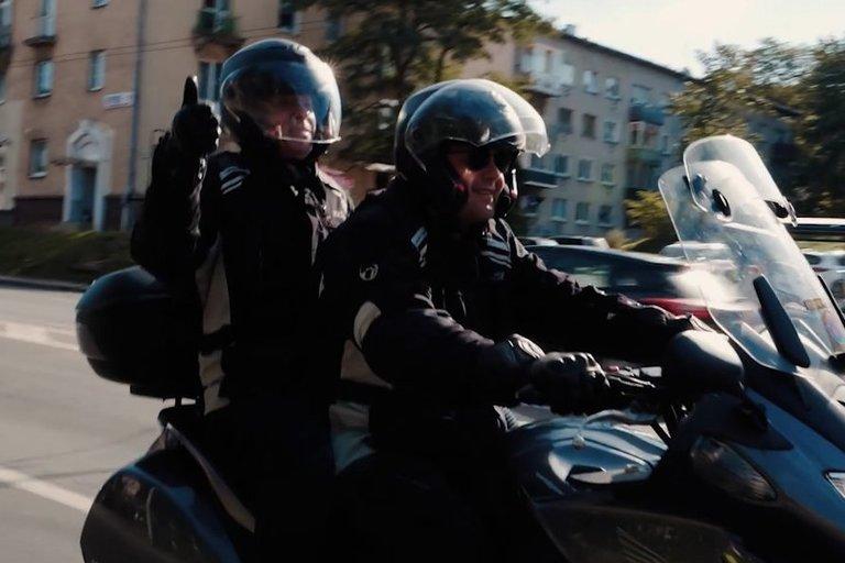 """Akcijoje """"Mane veža"""" dalyvauja motociklininkai ir regos negalią turintys žmonės. Vaizdo reportažo stop kadras."""
