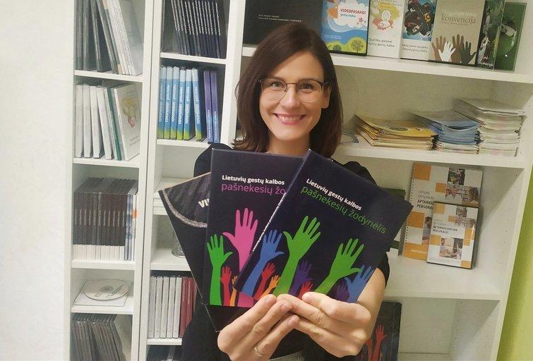 LGKI direktorė Ieva Stelmokienė demonstruoja instituto leidinį – lietuvių gestų kalbos pašnekesių žodynėlį. LGKI archyvo nuotr.