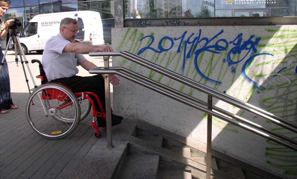 """Neįgaliojo vežimėliu judantys žmonės dažnai susiduria su nepritaikyta aplinka. Laikraščio """"Bičiulystė"""" archyvo nuotr."""